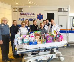 Emergency Medical services staff posing around a large collection of gifts